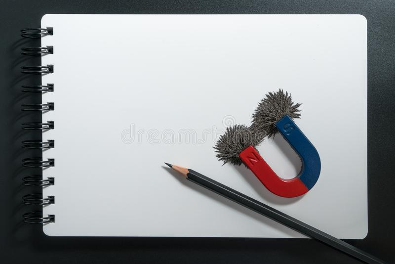 Red and blue horseshoe magnet or physics magnetic, pencil and compass with iron powder magnetic field on white paper notebook back stock photo