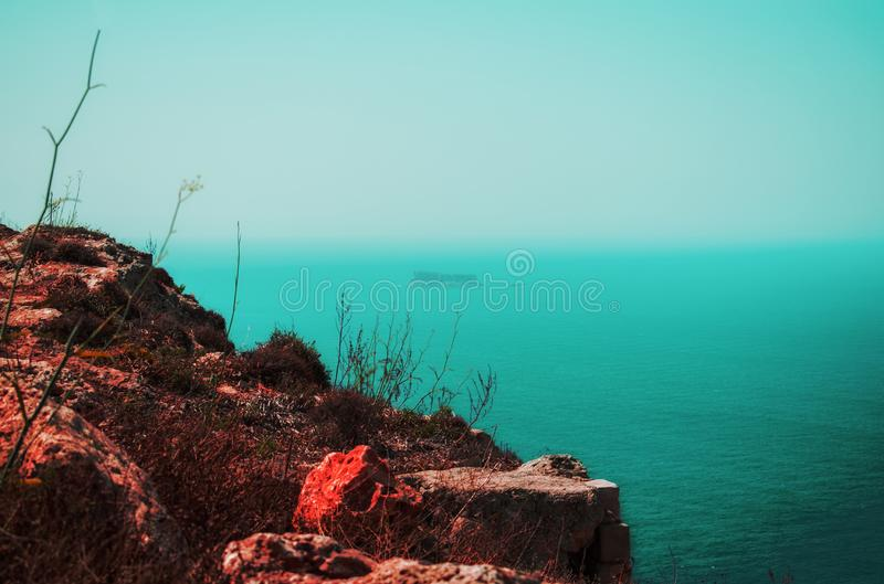 Red and Blue. A landscape from Dingli in Malta during a foggy day showing the contrast between the red rocks and blue sea including the island of Filfla royalty free stock images