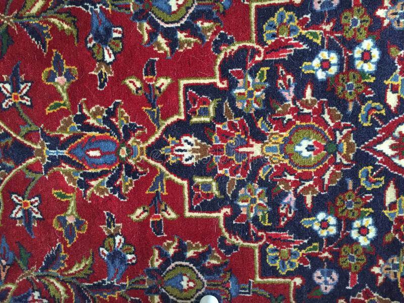 Red blue Persian rug on the floor with various shapes stock photos