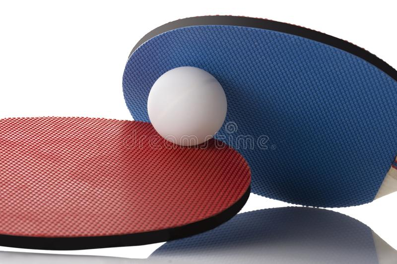 Red and Blue Ping Pong Paddles - Ball in between. A ping pong ball in between two Ping Pong Paddles, on white with reflection stock photo