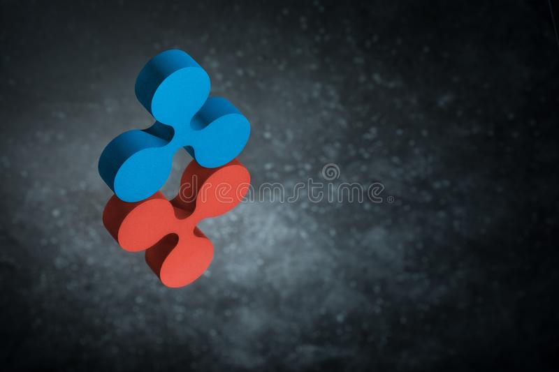 Red and Blue Ripple Currency Symbol in Mirror Reflection on Dark Dusty Background. Red and Blue Ripple Currency Symbol or Sign With Mirror Reflection on Dark stock images