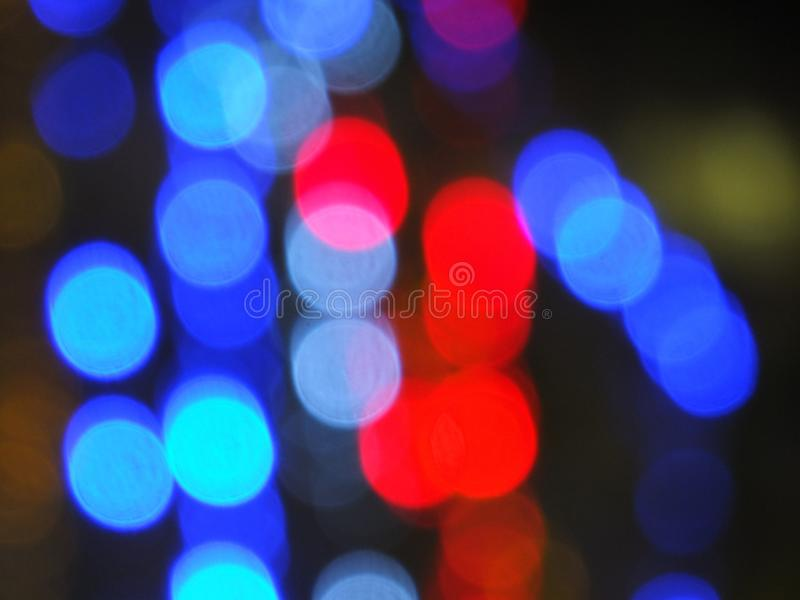 Red and blue round blurred lights at night. Red and blue round blurred city lights at night on a dark background stock photography