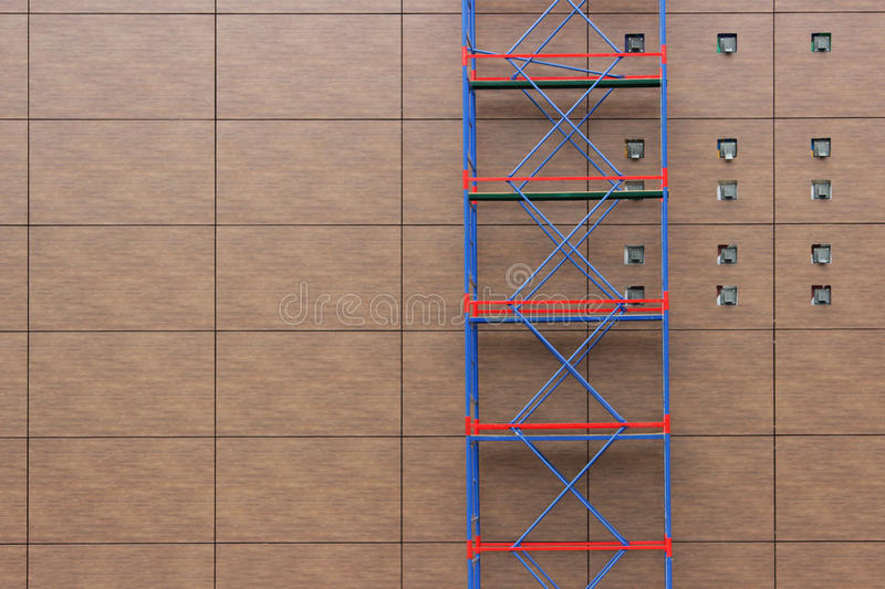 red-blue scaffolding on a background of brown panels on the wall of a shopping mall during a renovation stock image