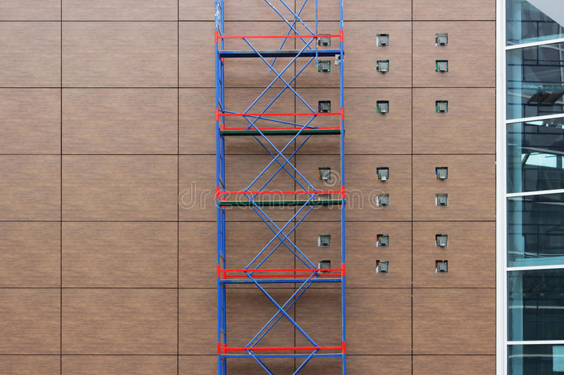 red-blue scaffolding on a background of brown panels on the wall of a shopping mall during a renovation stock photo