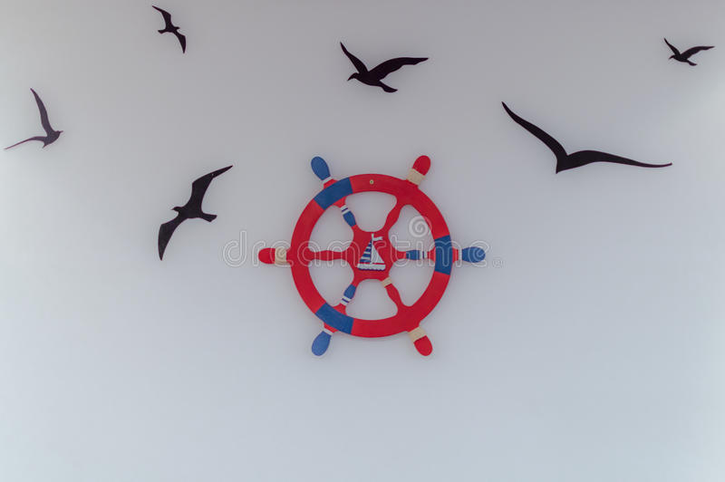 Red blue ship's steering wheel and flying birds - illustration on wall.  stock images