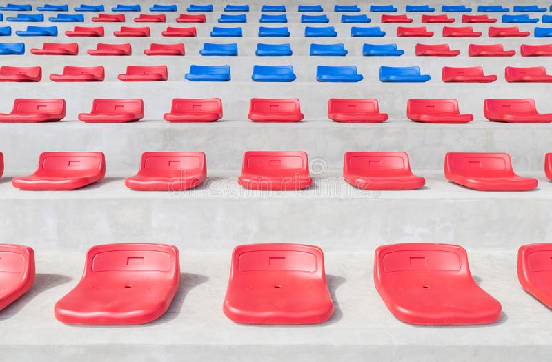 Red and blue sport plastic seats grandstand in public sport stadium. Rows of empty red and blue sport plastic seats grandstand in public sport stadium stock photo