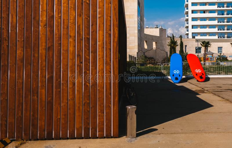 Red and Blue Surfboards Near Brown Wooden House stock photography