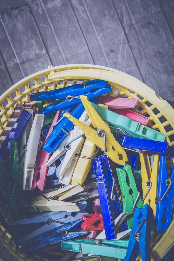 Red Blue Teal Green and Yellow Clothes Pin in Yellow Plastic Bucket stock photo