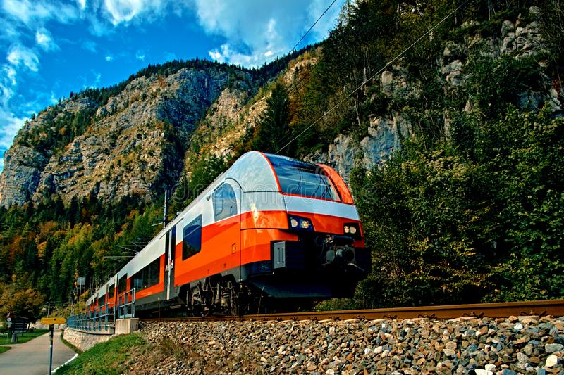Red blue train in motion in Austrian alps mountains. High speed mountain train arrives at Hallstatt Obertraun train station royalty free stock images