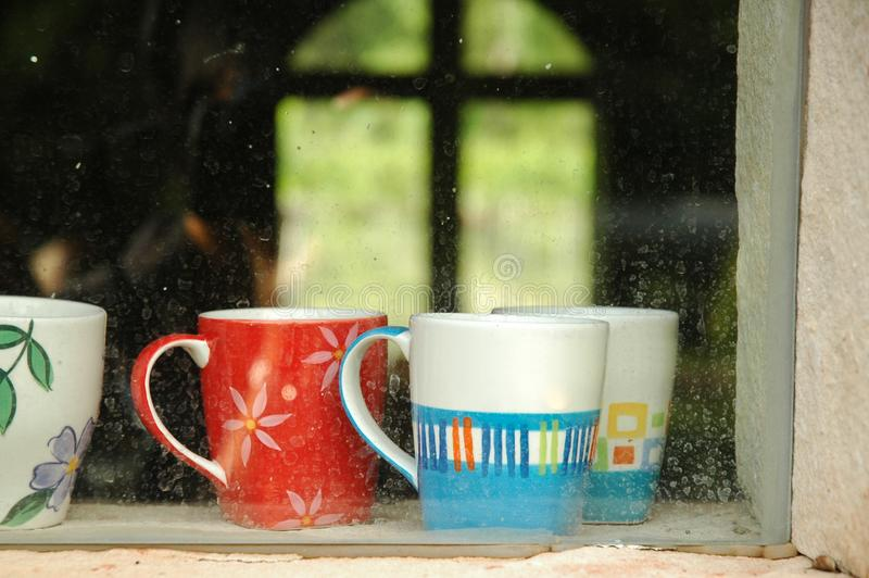 Warm coffee cups inside a window of a cozy house royalty free stock image