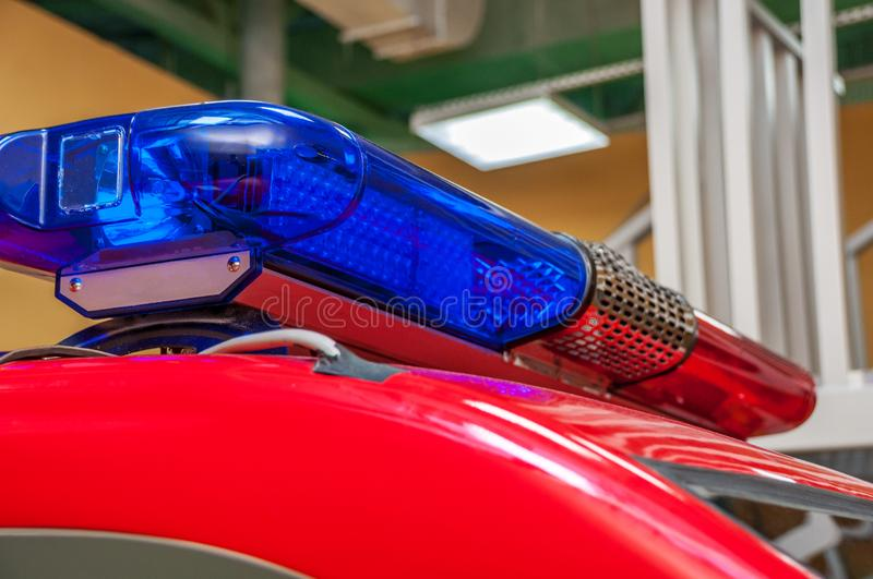 Red blue warning with long siren on car roof. Standing in garage turned blue side closeup with blurred background royalty free stock image
