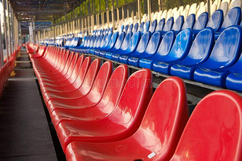 Red, blue and white sports stadium seats. Empty stands, no spectators at the competitions.  stock photography