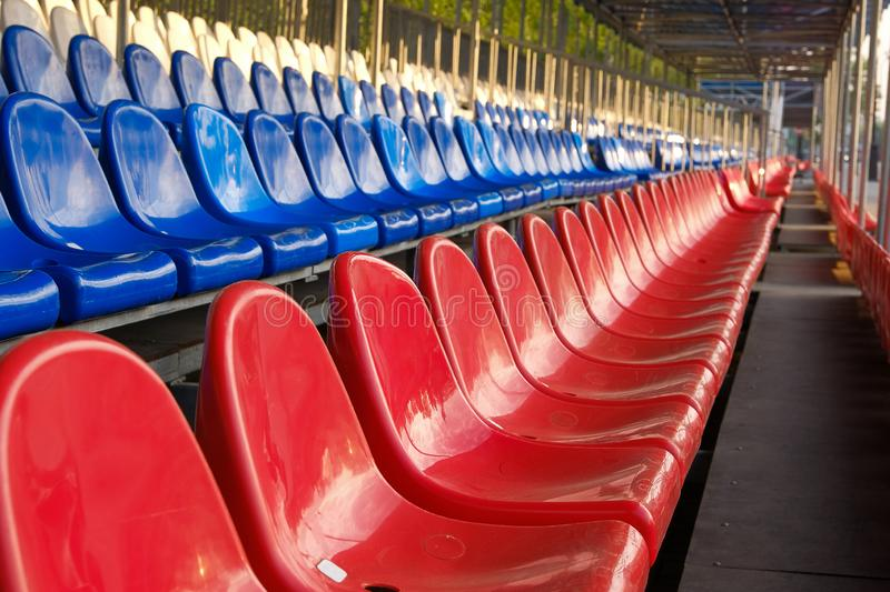 Red, blue and white sports stadium seats. Empty stands, no spectators at the competitions.  royalty free stock photography