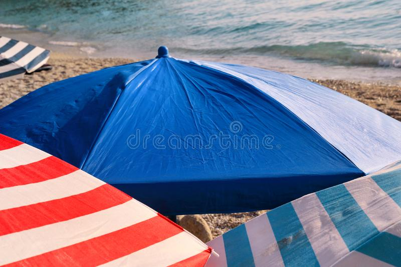 Red, blue and white sun umbrella for sunbathing and protection of sun rays, closeup. Colorful parasol beach umbrella. stock photos