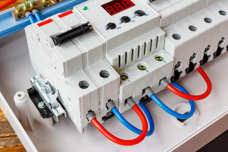 Red and blue wires connected to the ports of voltage limiter and double input automatic circuit breaker closeup royalty free stock image