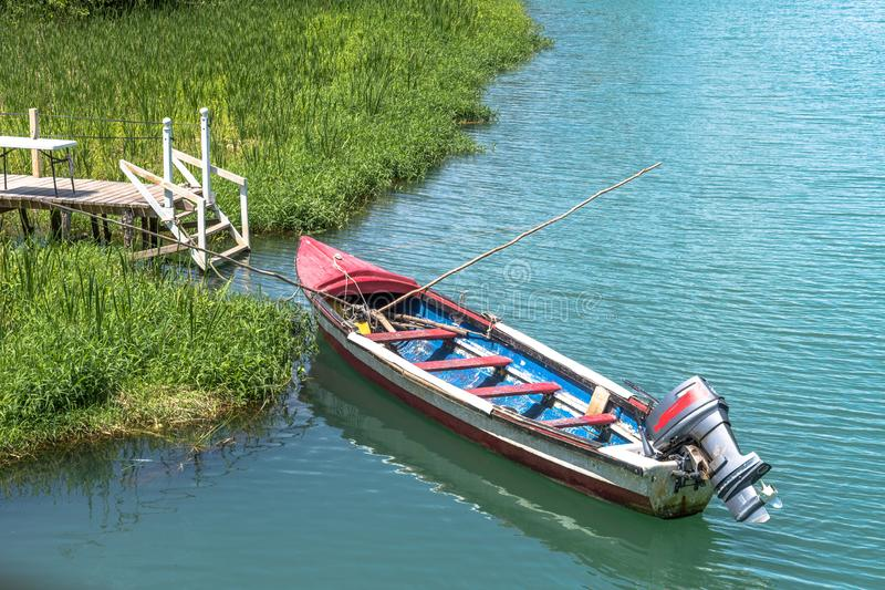 Wooden fishing boat with stick fishing poles. Red and blue wooden fishing boat with stick fishing poles, docked by river bank royalty free stock image