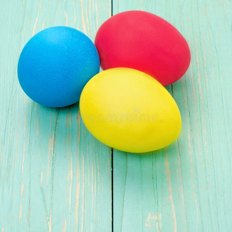 Red, blue, yellow Easter eggs. Three multicolored handmade easter eggs on a blue wooden background. Square. royalty free stock images