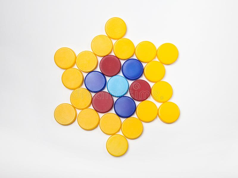 Red, blue, yellow, plastic bottle caps are lined up in the shape of a star stock photos