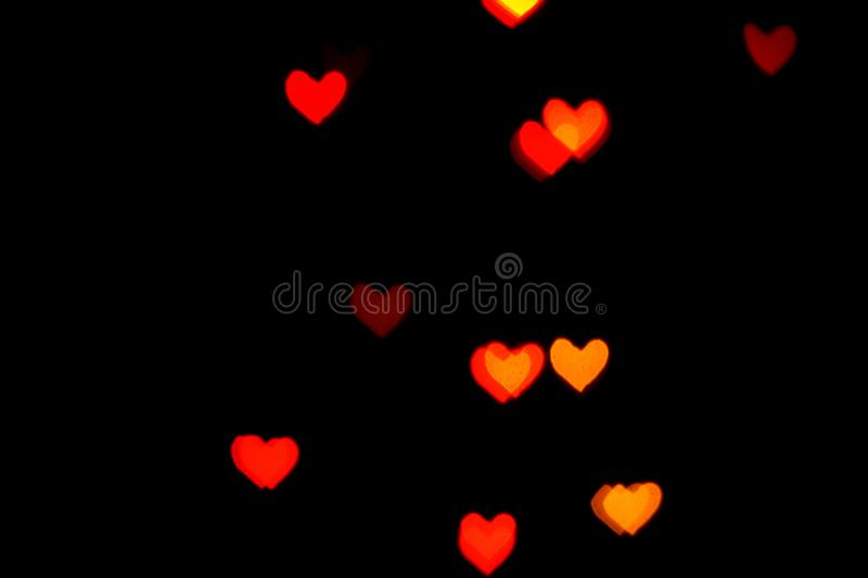 Red blurred lights in the shape of hearts in the dark royalty free stock photos