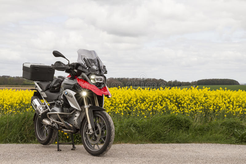Red BMW R1200GS in a field. A red BMW R1200GS TE motorcycle showing a field and a cloudy sky. LED headlight and spotlights, screen and red beak. Top case stock photography