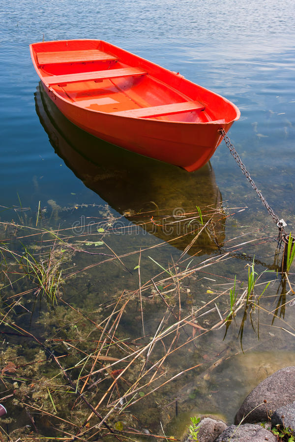 Red boat. With chain on a lake royalty free stock photo