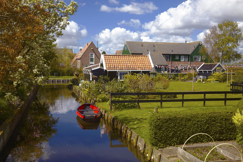Red boat on the calm water of a canal and traditional wooden buildings in Marken, Holland stock photo