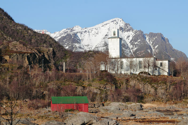 Red boat house and Stamsunds Church. Wooden cabin on the beach of Stamsund in Lofoten, the Stamsund church on the background royalty free stock photo