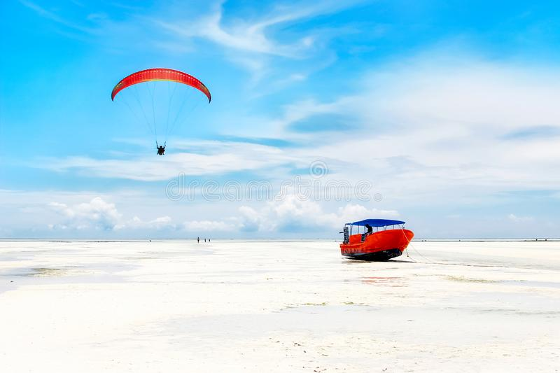 Red boat and red parachute on the beautiful white beach. stock image