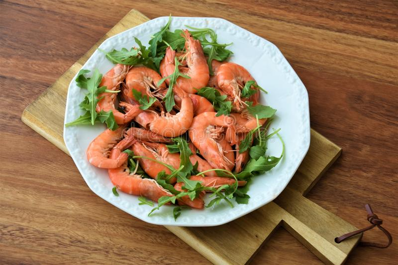 Red boiled big shrimps with unpeeled heads with rucolla leaves stock photography