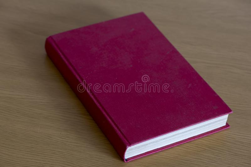 A red book closed on the table. A red book closed on the brown table stock photography