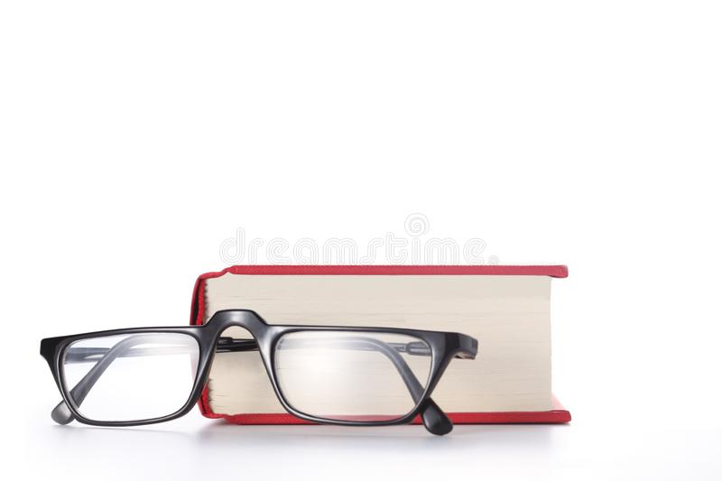 Red book and eye glasses isolated on white background with copy space for your text. Red book and eye glasses isolated on white background with copy space stock photos