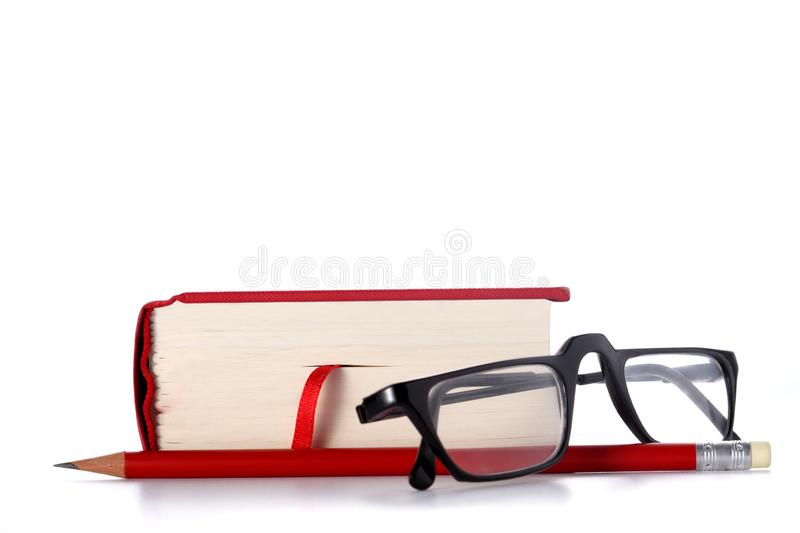 Red book, eye glasses and a red pencil isolated on white background with copy space for your text. Red book, eye glasses and a red pencil isolated on white royalty free stock photography