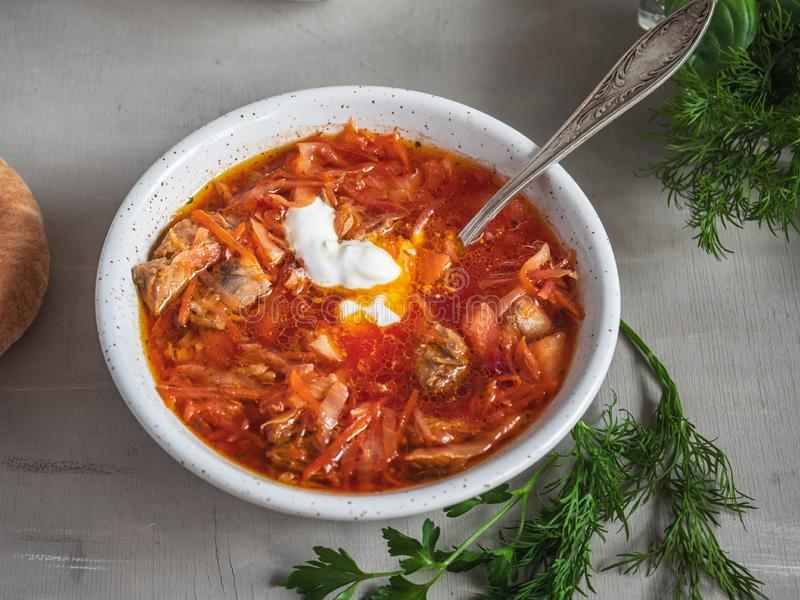 Red borsch with a tablespoon is shot at close range. A few sprigs of dill on a gray background stock photo