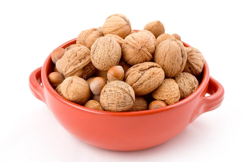 Red bowl with mixed nuts, walnuts, hazelnuts, almonds royalty free stock image
