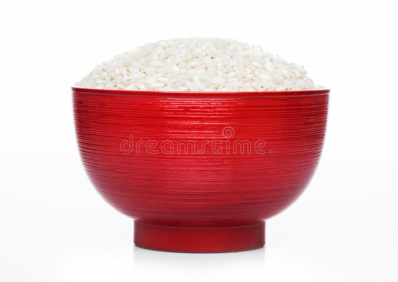 Red bowl of raw organic arborio risotto rice on white background. Healthy food stock image