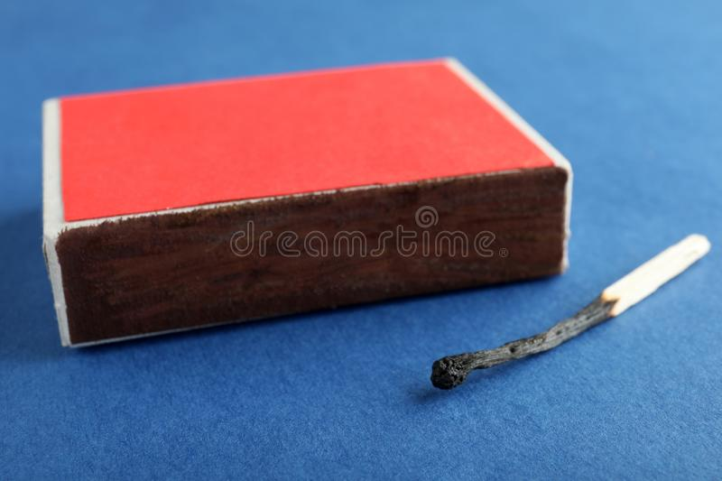 Red box and burnt match on color background stock images