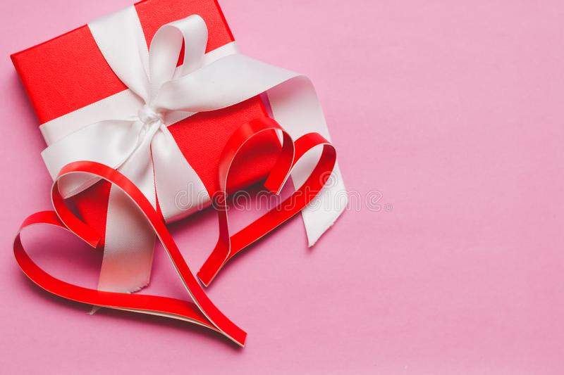 Red box with a gift, tied with a white ribbon, and red homemade paper hearts on a pink background. Symbol of Valentine`s Day royalty free stock photo