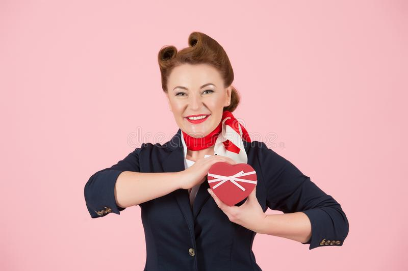 A Red box with ribbon in hand of brunette woman. Box for present in hand of beautiful airhostess. Valentine concept female stock photo