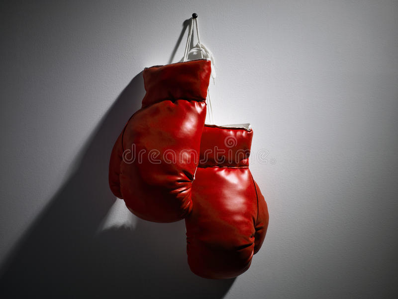 Red Boxing Gloves. One pair of red boxing gloves hanging from the wall stock photography