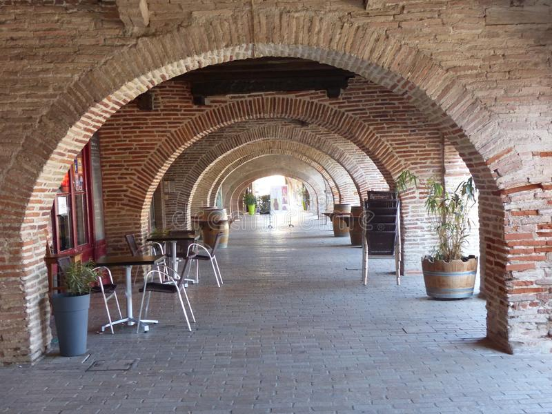 Red brick arches of a ground floor of ancient buildings to Lisle sur Tarn in the south east of France. Sunny day. Springtime  and holidaytime. Characteristic royalty free stock photography