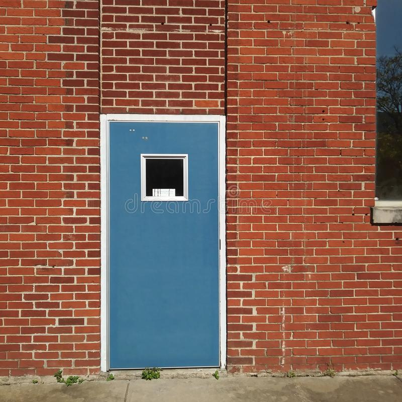 Red Brick Building Exterior Wall and Blue Door Background. stock photo