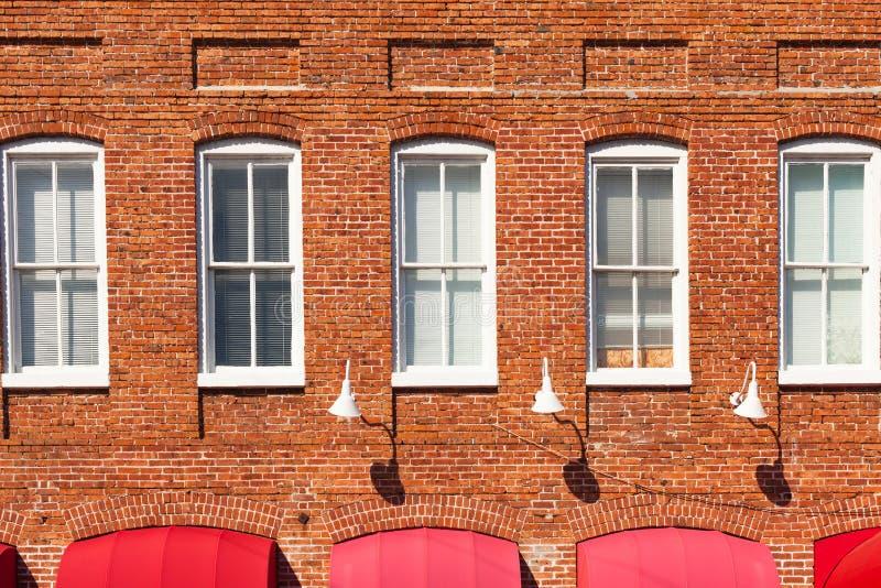 Red Brick Building Facade. With white windows stock photos
