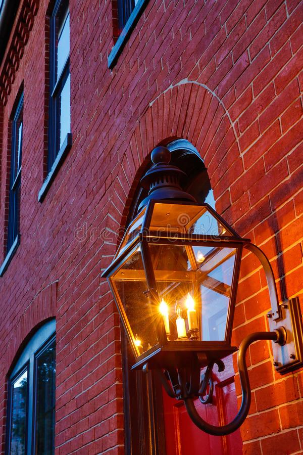 Red brick building facade with light in forground. As architectural detail stock image