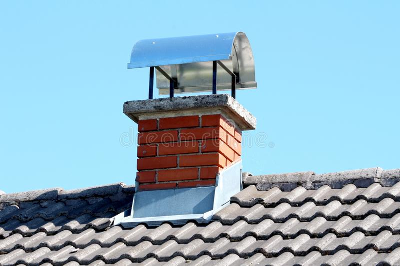 Red brick chimney with shiny metal top protection on new house roof surrounded with dark grey roof tiles and clear blue sky in stock images