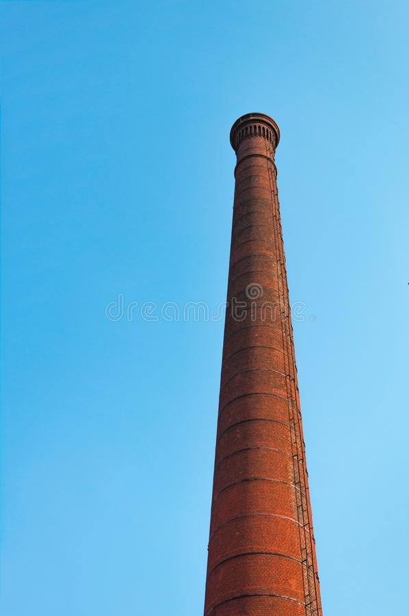 Red brick factory pipe against blue sky. The concept of environmental pollution by harmful emissions into the atmosphere royalty free stock images