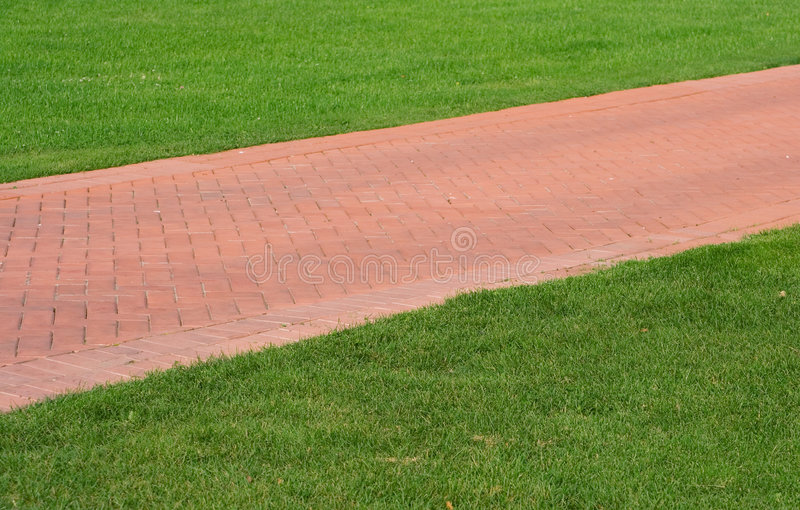 Red brick footpath. On green lawn. summer landscape royalty free stock photo