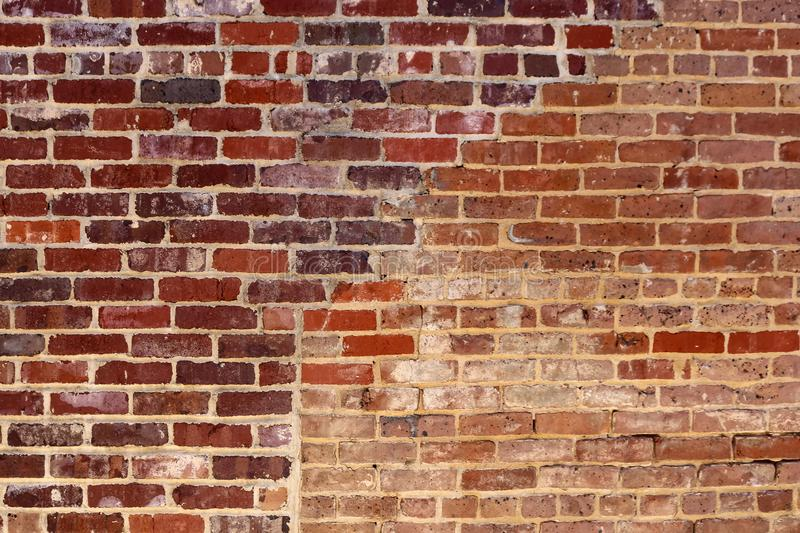Red brick grunge background with an area that used to be an opening filled in with different bricks stock images