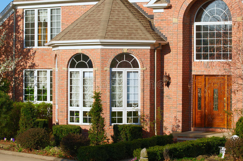 Red brick home. A large red brick residence with fancy entrance and bay window royalty free stock image