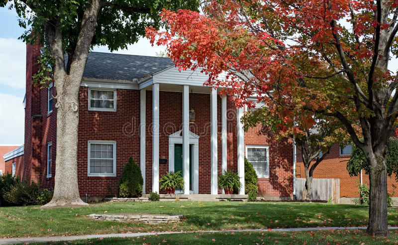 Red Brick Home with Tall Pillars. Urban, red brick house with tall white pillars in fall royalty free stock photography