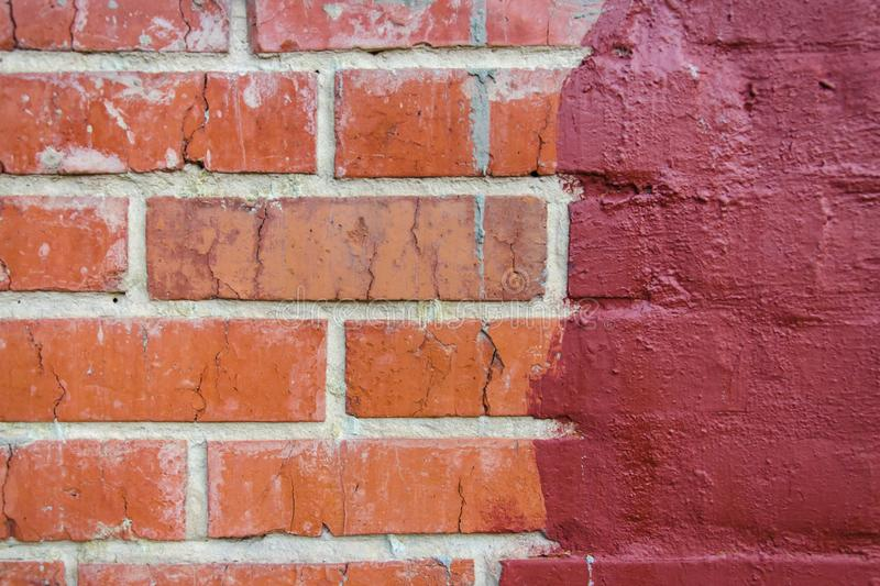 Red brickwork half painted in dark red paint stock images